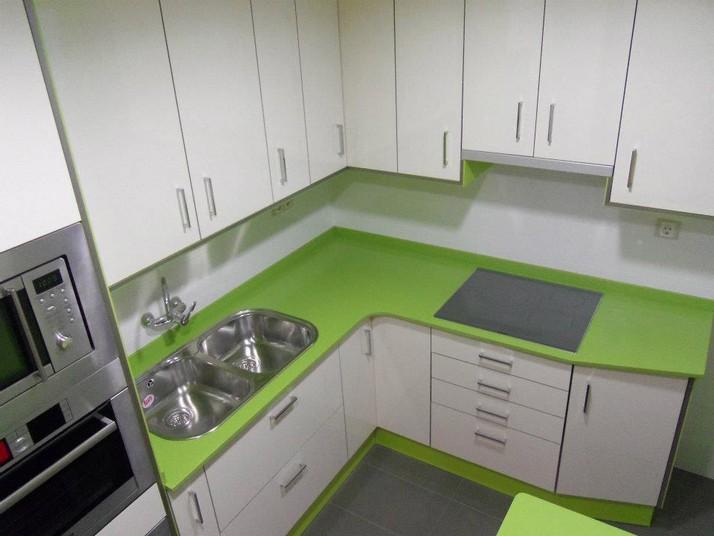 Encimera silestone color verde y muebles en blanco brillo