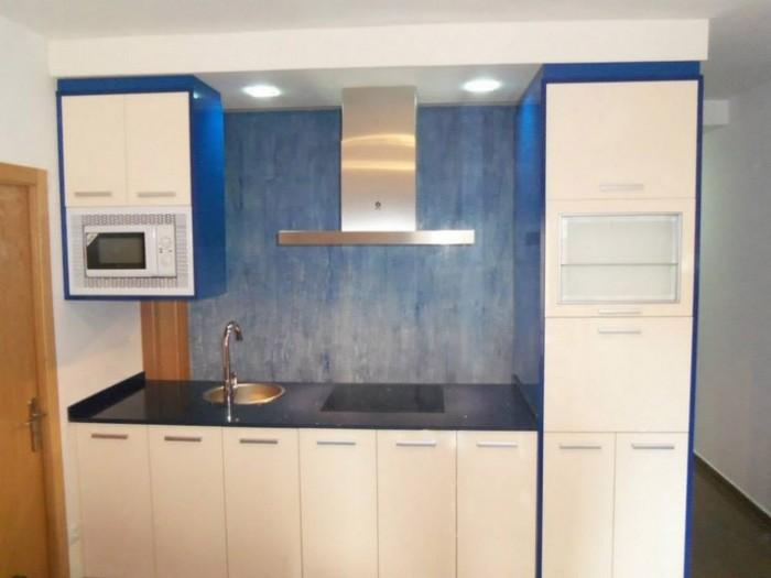 Cocina isla azul en forma de isla con muebles de color marfil brillo