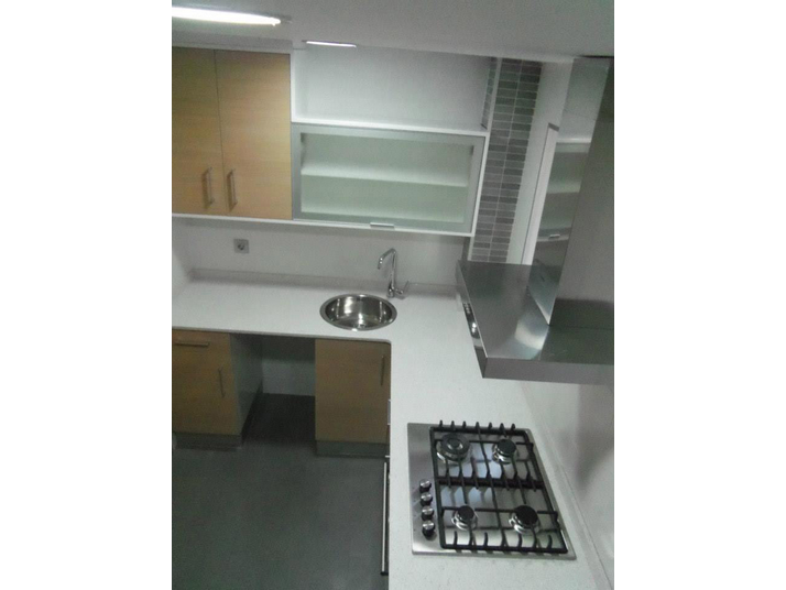 Muebles de cocina en roble claro enmarcado en blanco brillo y encimera de color blanco