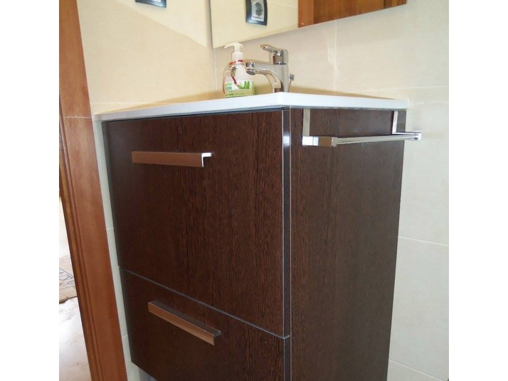 Mueble en color roble oscuro con toallero incorporado a un lado
