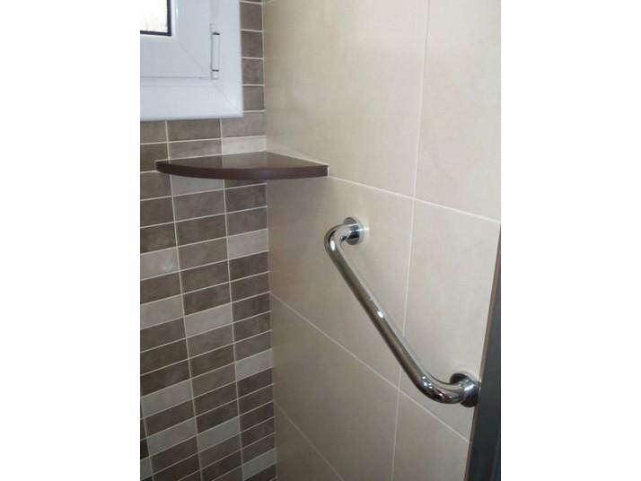 Detalle del estante en Silestone mod. Gedatsu, de tonalidad marrón, junto a la asa de ducha.