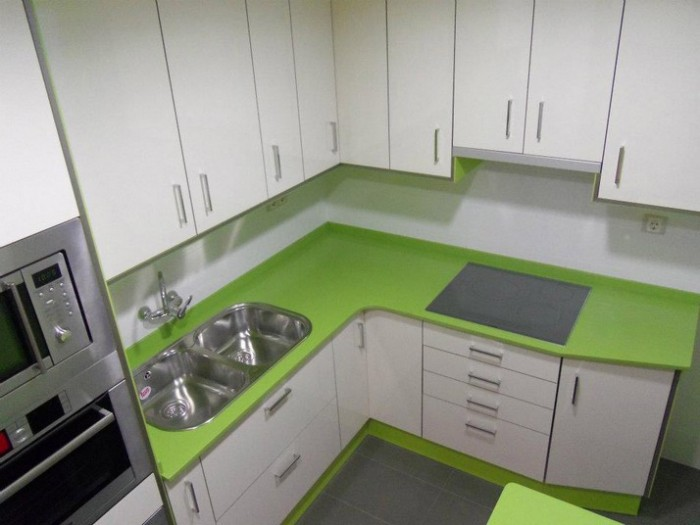 Encimera silestone color verde y muebles en blanco brillo