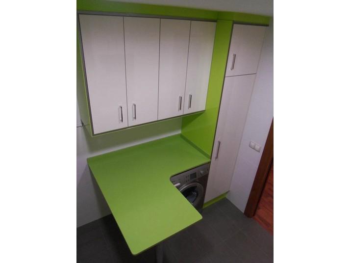 Zona para la colada en verde pistacho y muebles de cocina en blanco brillo