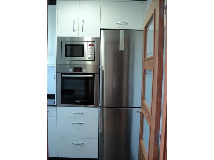 Electrodomésticos plateados con muebles de cocina en color blanco luxe