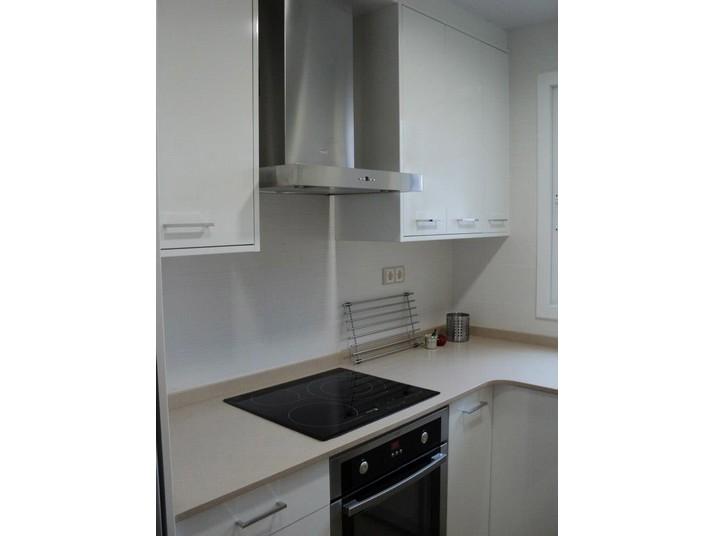 Encimera de color beige con placa de inducción; muebles de cocina en blanco