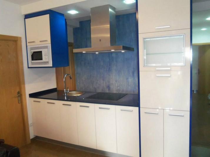 Cocina en forma de isla con muebles en color marfil brillo y costados en azul marino